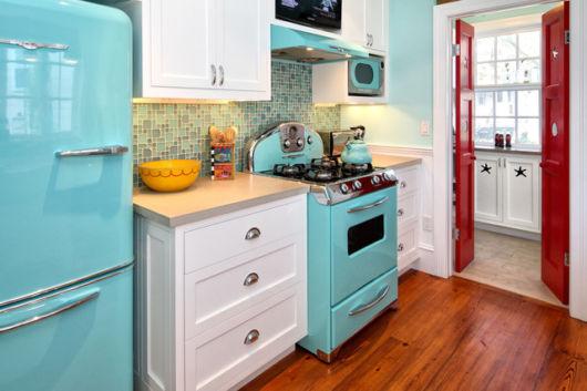 Fogão azul claro combinando com a geladeira da mesma cor e com os móveis em branco