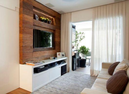 O painel de madeira na TV traz requinte a esse ambiente instalado próximo à sacada do apartamento