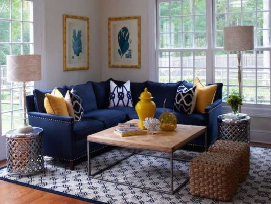 O sofá azul destaca o ambiente com a decoração em marrom e amarelo