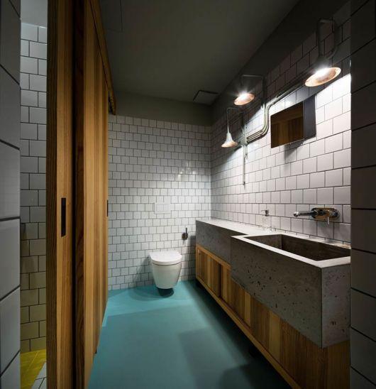 Nesse modelo de decoração, o piso azul destaca a decor em branco e marrom do banheiro