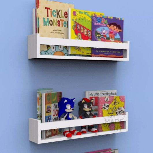 Dois nichos/prateleiras instalados na parede com vários livros e bonecos