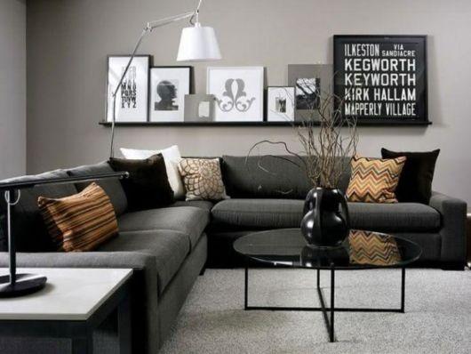 Combinando perfeitamente com a parede cinza, o sofá e a mesa de centro pretos