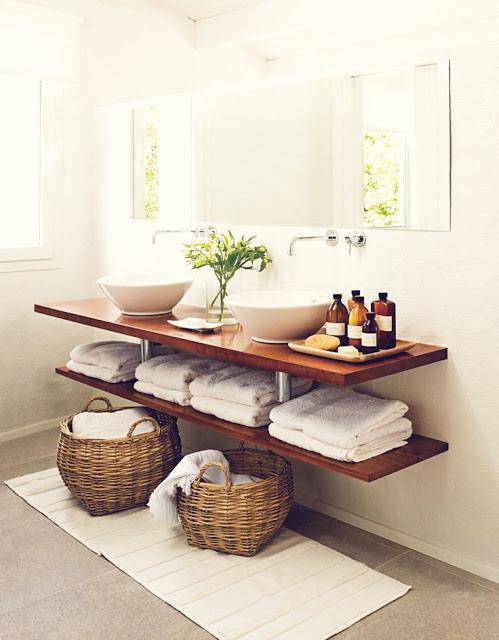 Um ótimo exemplo de decoração e organização com uma bancada de madeira para banheiro simples