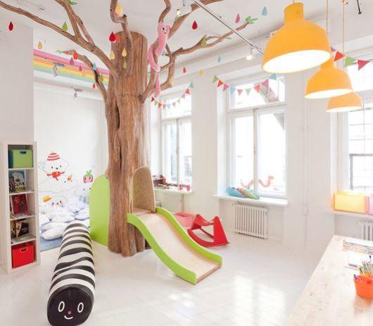 Temáticas criativas são, sem dúvidas, belos exemplos para todos os projetos como essa árvore montada ao centro com um escorregador