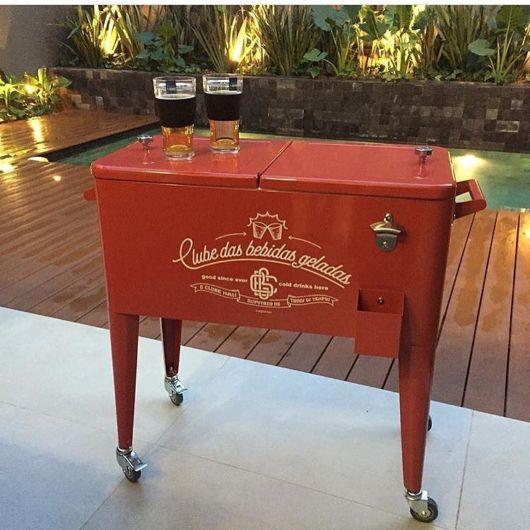 Cooler grande e vermelho com rodinhas que ainda funciona como mesa