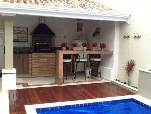 deck e bancada de madeira com churrasqueira
