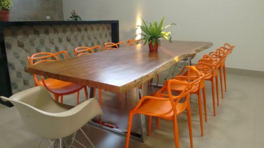 Mesa grande com cadeiras laranjas