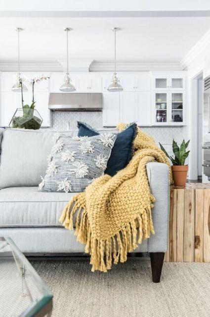 Sala com sofá cinza com manta amarela.