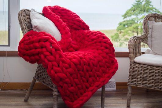 cadeira cinza com manta de croche vermelha.
