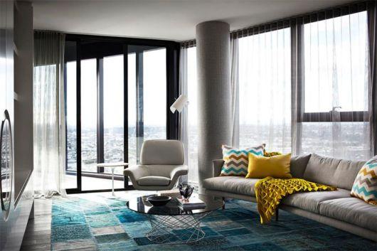 Sala grande com sofá bege e manta amarela.