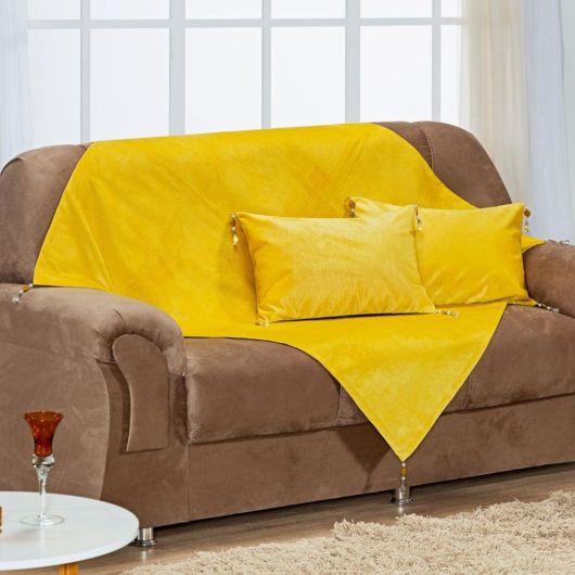 Sofá com manta amarela triangular.