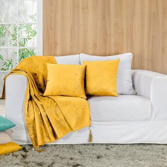 Sofá branco com manta amarela.