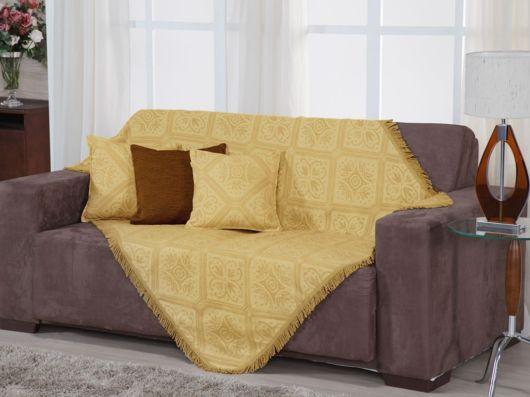sofá marrom com manta amarela e almofadas.