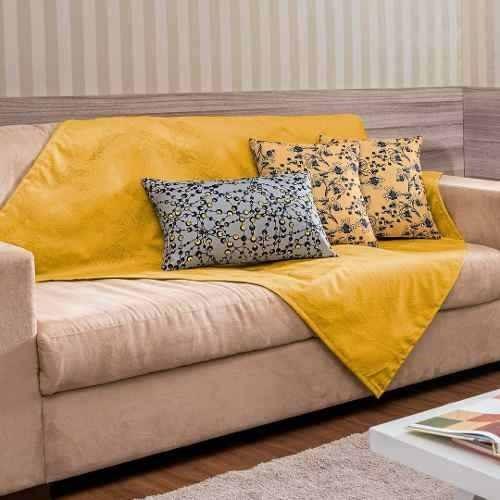 Sofá bege com amanta amarela vibrante.