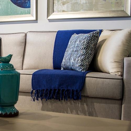 sofá bege com manta azul.
