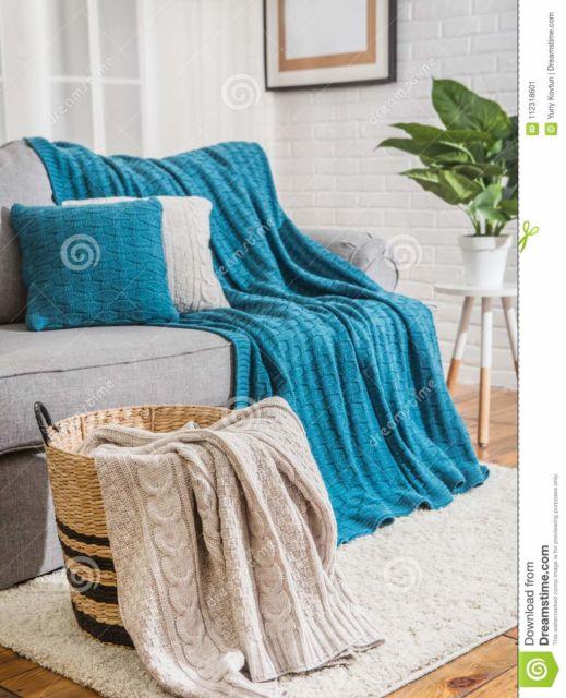 Sofá bege com manta azul turquesa.