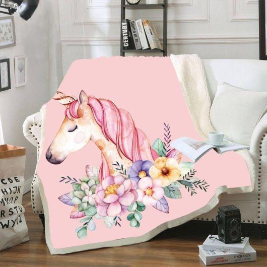 Manta cor de rosa com detalhes bordados.