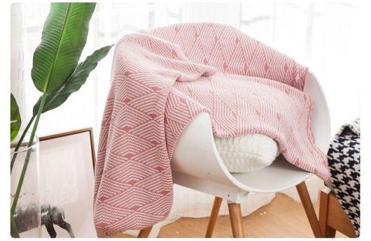 Poltrona branca com manta cor de rosa.