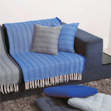 Manta azul claro colocada em sofá azul escuro.