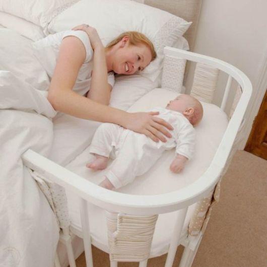 Mãe acariciando bebê que está em berço anexo à cama.