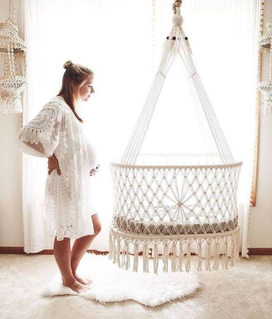 Mulher grávida olhando berço suspenso.