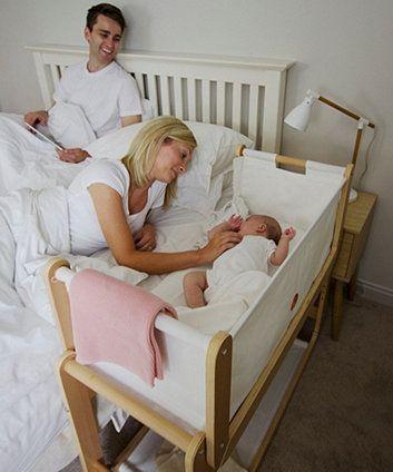 Pai e mãe olhando bebê no berço próximo à cama.