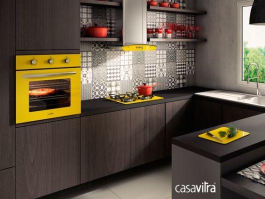 Cozinha com cooktop e forno amarelos.