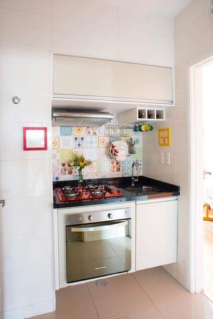 Cozinha pequena com azulejos coloridos e cooktop vermelho.