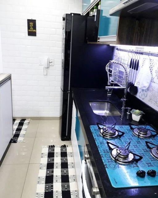 Cozinha branca e preta, com cooktop colorido.