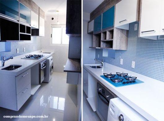 Cozinha branca com cooktop e armários azuis.