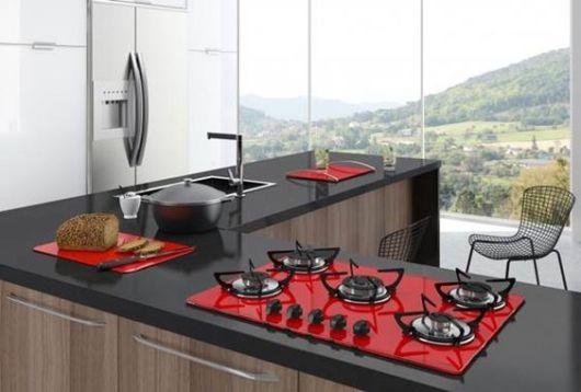 Cozinha americana com pia de granito e cooktop vermelho.