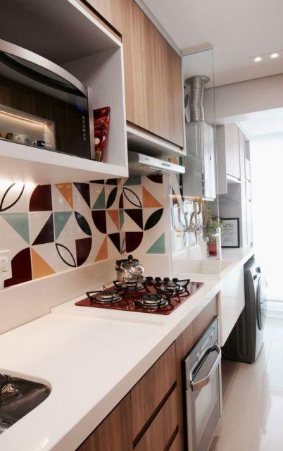 Cozinha com bancada ampla e cooktop colorido.