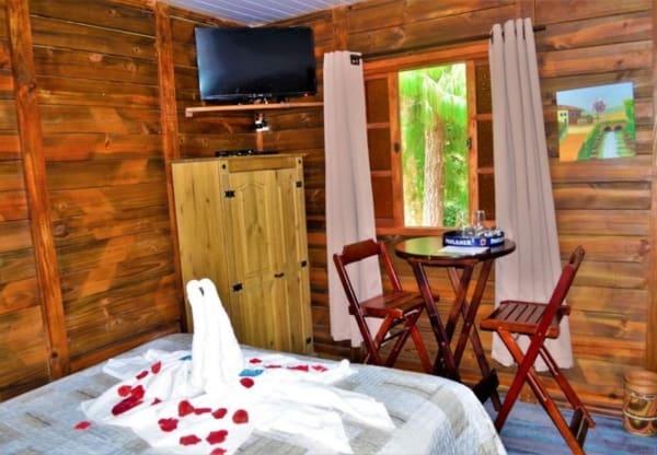 Área interna do chalé de madeira com mesa e TV