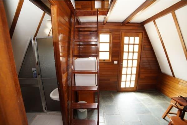 Área interna de chalé de madeira com escada