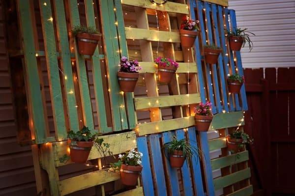 parede de pallet com luzes pisca pisca e plantas