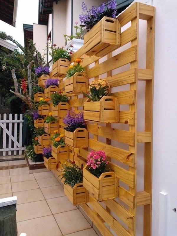 Parede de pallet decorada com plantas em caixotes