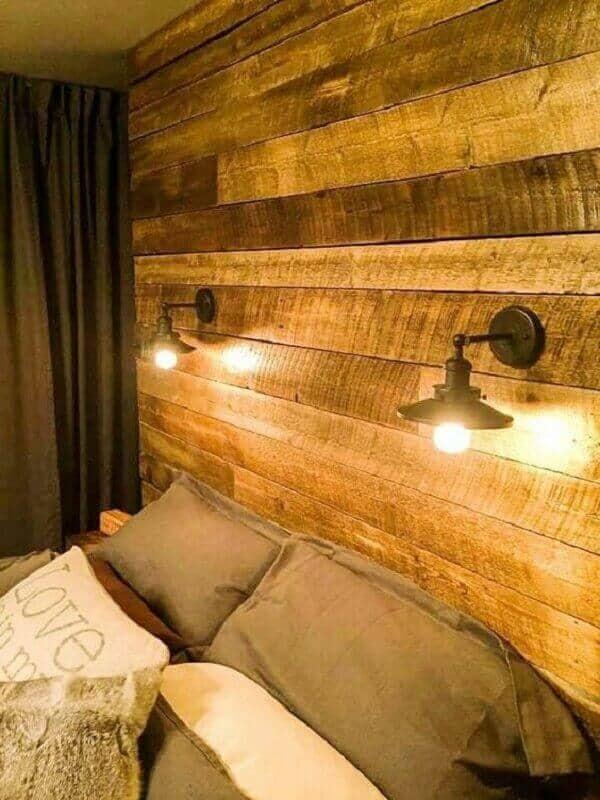 parede de pallet no quarto com arandelas