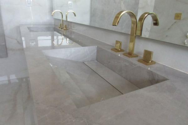 pia de banheiro com torneira dourada