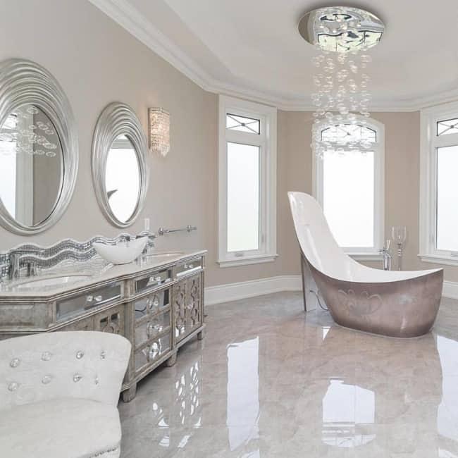 Banheiro clássico luxuoso com lustre de cristais pendente e banheira extravagante