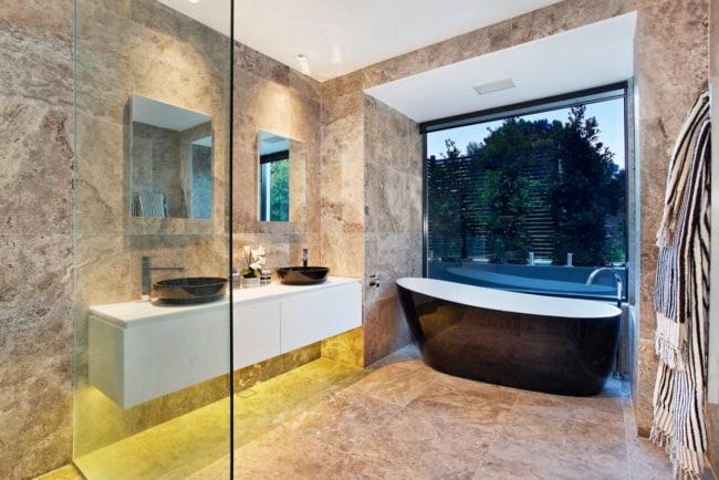 Banheiro com banheira e piso de mármore travertino