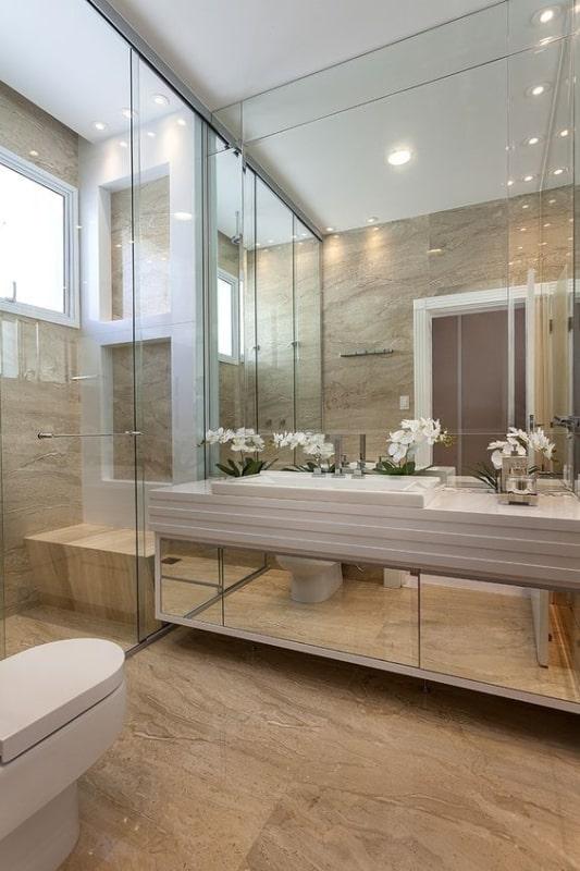 Banheiro com piso de mármore travertino e armário espelhado 1