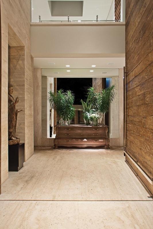 Hall de entrada com piso e parede de travertino