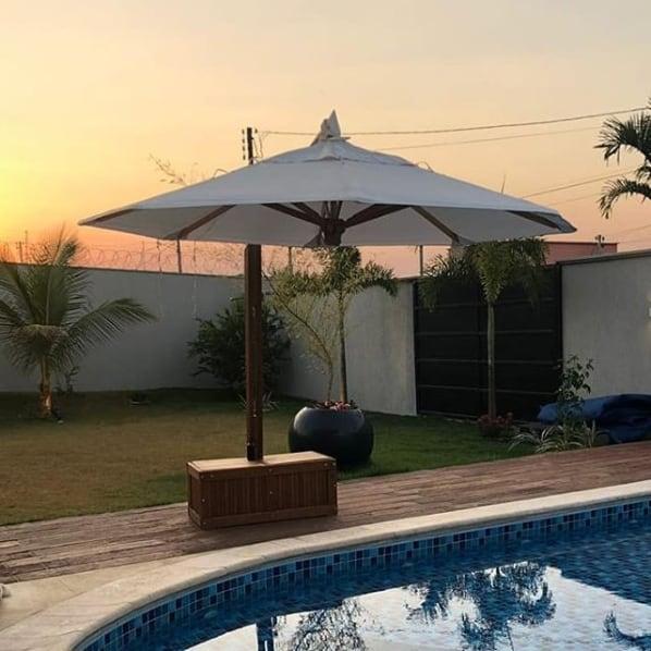 área da piscina com ombrelone de madeira