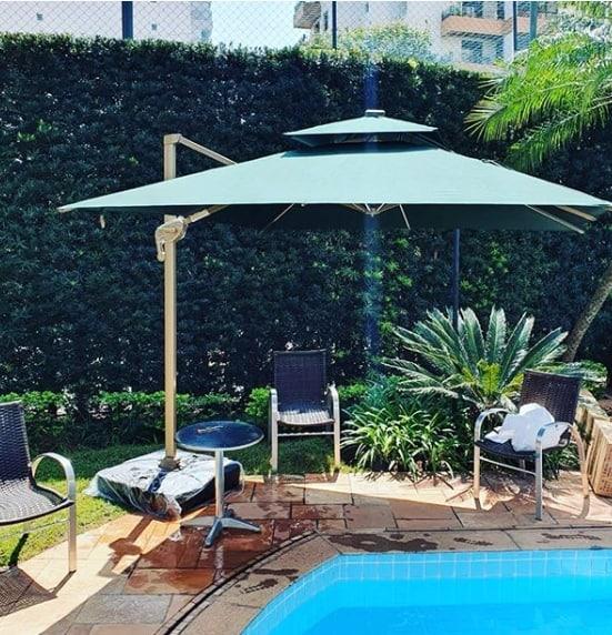 piscina com cadeiras e sombra