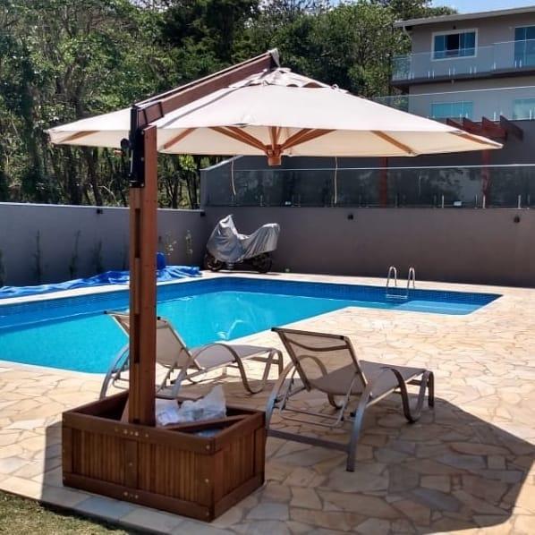 área da piscina com guarda sol e espreguiçadeiras