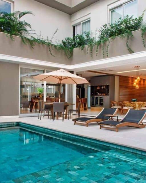 área da piscina com mesa e ombrelone