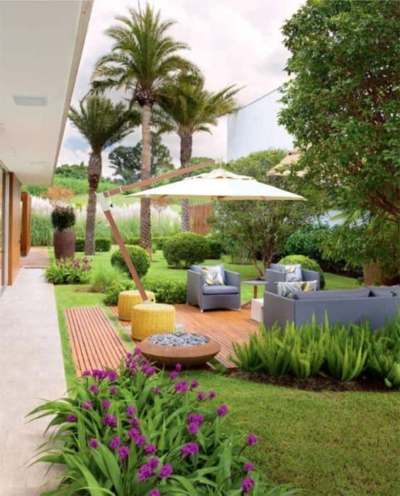 jardim com deck de madeira e sofás