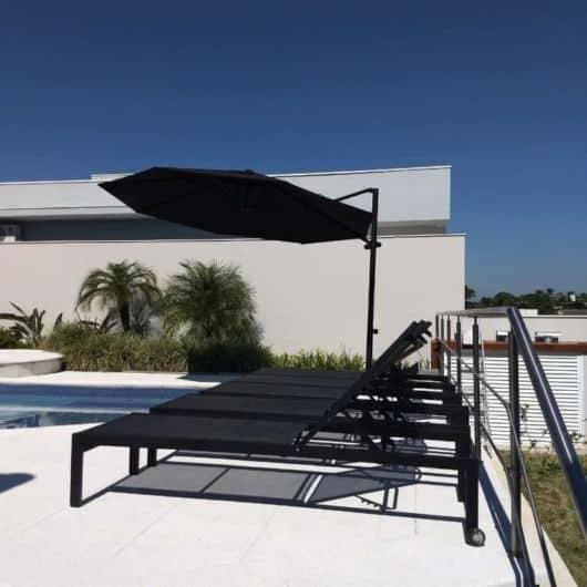 piscina com espreguiçadeiras e ombrelone preto