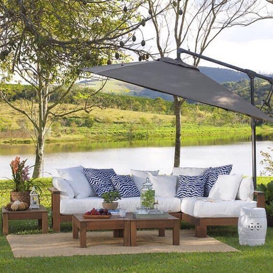 jardim decorado com sofá e guarda sol