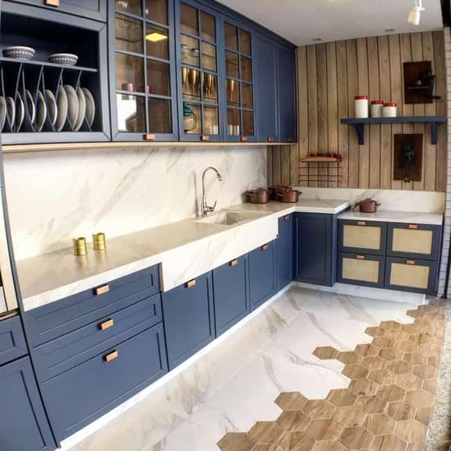 Bancada marmorizada branca e armários azuis na cozinha